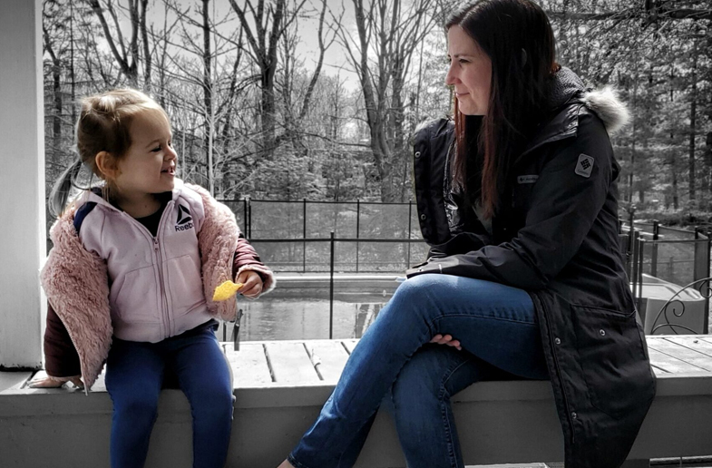 Woman and her young daughter sit on an outside bench in winter